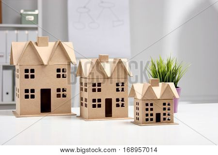 Miniature houses on the desk in office .