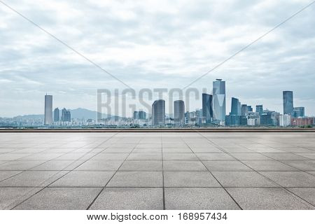 modern office buildings in seoul from empty brick floor in cloud sky