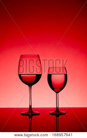 two wine glasses filled equally with liquid