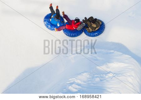 Happy children on toboggans, snowy slope at ski resort, winter leisure, active lifestyles, childhood, Christmas. Light background with copy space
