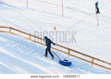 Young man pulls toboggans on snowy slope at ski resort, winter leisure, active lifestyles, childhood, Christmas. Happy hobby. For background, place text