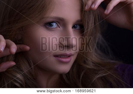 face of a beautiful blond girl looking seductively straight to the camera dark tones low key