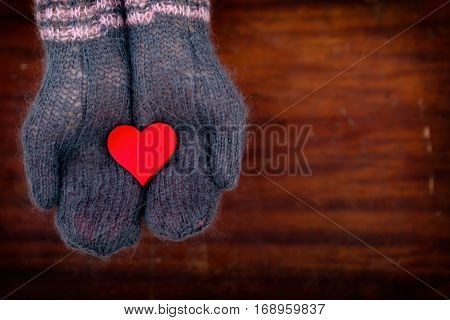 one red heart in hands in mohair gloves on wooden background