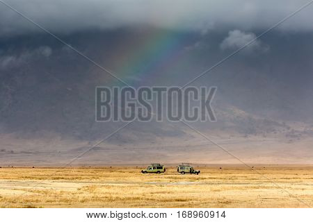 Game drive. two safari cars on game drive with animals around and a rainbow, inside Ngorongoro crater in Tanzania