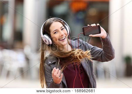 Fashion girl dancing and listening music showing a blank screen of a smart phone and looking at you in the street