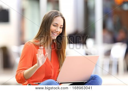 Happy woman talking on line in a video conference with a laptop sitting on a bench in the street