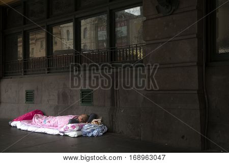 MELBOURNE, AUSTRALIA - OCTOBER 14, 2016:  Young homeless man sleeping in a pink sleeping bag on pavement.  Record numbers of homeless people sleeping on Melbourne's streets.