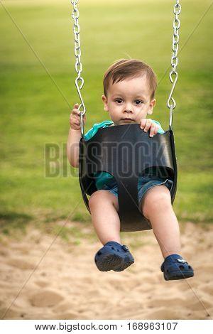 happy baby swinging on swing at children playground