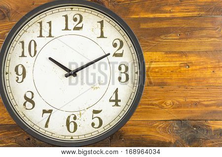 A wall clock at ten and ten minutes on wooden background