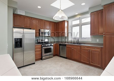 Kitchen in condominium with cherry wood cabinetry.