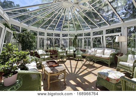 Sun room in luxury home with green wicker furniture.