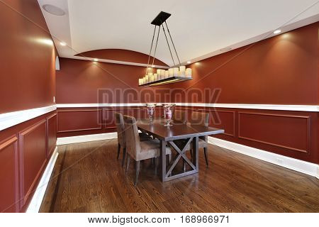 Dining room in upscale home with orange walls.