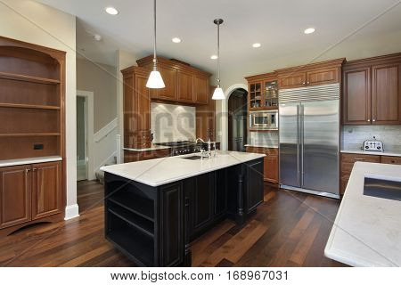 Kitchen in luxury home with dark wood island.