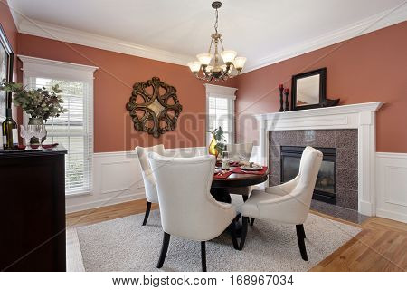 Dining room with orange walls and marble fireplace.