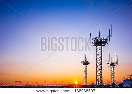 many airport communication towers at the sunset