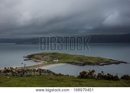 North Coast Scotland - June 6 2012: Small green island in Loch Eriboll connected with a short dam and featuring a white fisherman house. Cloudy foggy sky bluish water mountainous background.