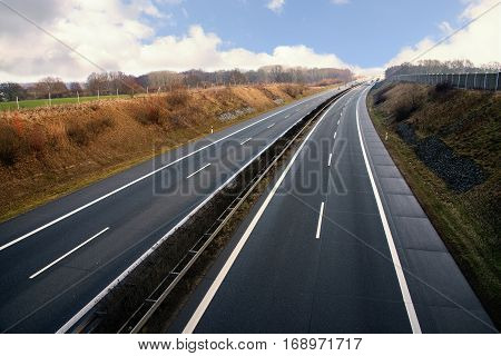 Highway runs through a rural landscape in northern Germany also called german autobahn
