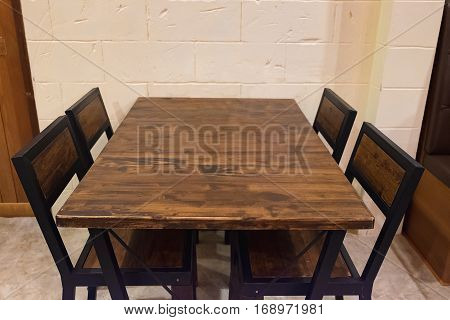 Oak Dining Table With Chairs In Dark Room.