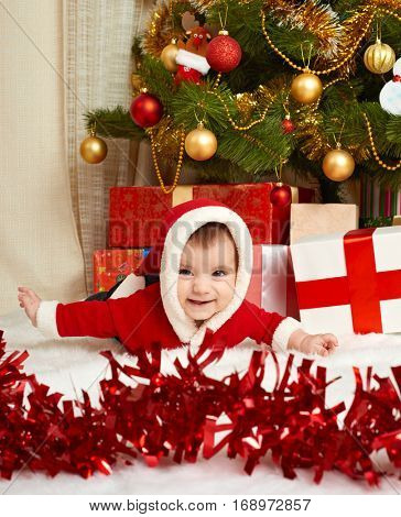 happy baby portrait in christmas decoration, lie on fur near fir tree and gifts, winter holiday concept