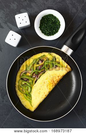 Omelette with green bell pepper and red onion in frying pan photographed overhead on slate with natural light