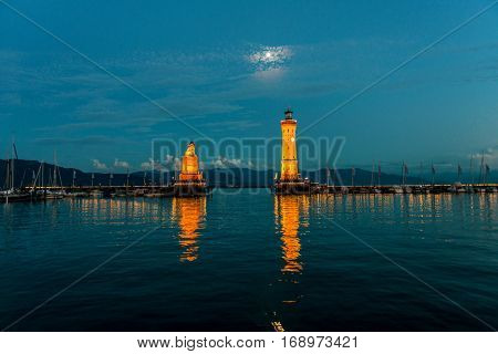 Night view of the entrance to Lindau harbor with the historic lighthouse and lion statue illuminated by glowing lights reflected in the water of Lake Constance