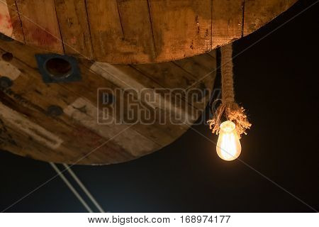 tungsten lamps old fashion chandelier with circle wooden ceiling decoration in dark room. selective focus