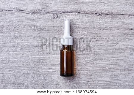Nasal spray on wooden backdrop. White plastic cap on bottle. Always stay healthy.