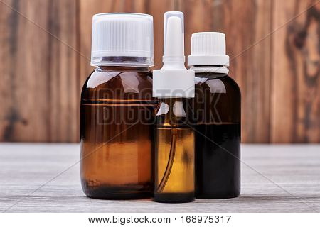 Vials with medicine on wood. Nasal spray and cough syrup.