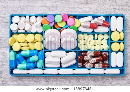 Pills and capsules in container. Medical remedies for patients.