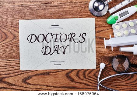 Aids and card on wood. How to congratulate your doctor.