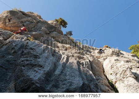 Man climbing on a limestone wall, rock and sky on the background