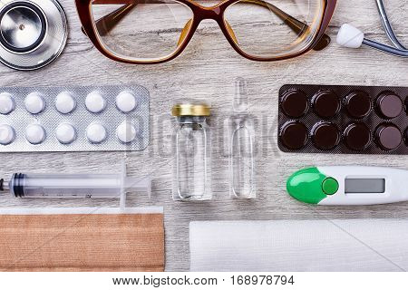 Doctor's instruments on wooden backdrop. Set of remedies.