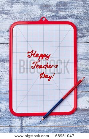 Clipboard and double pencil. Laconic congratulation to Teacher's Day.