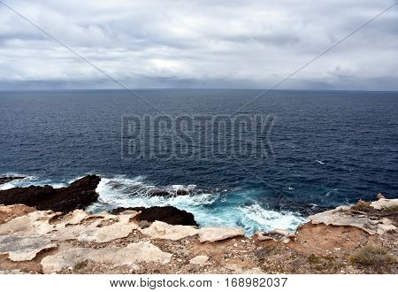 Gushing sea on a cloudy day. Horizontal view of overcast sky and sea. Fifty shades of blue. Waves breaking on the ocean rocks.
