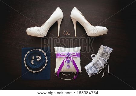 White wedding bridal shoes with high heel and accessories on dark wooden background top view