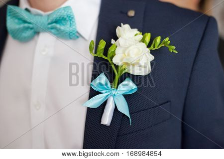 Colorful wedding boutonniere on suit of groom closeup