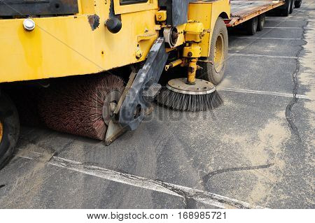 close up on road sweeper cleaning sand in parking lot