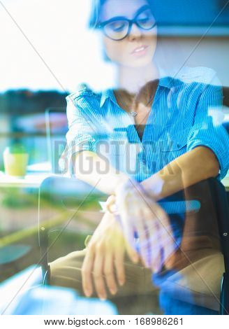 Young woman sitting at office table with laptop, view through window