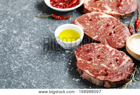 Raw fresh meat Ribeye Steak with rosemary pepper and sea salt on stone slate background with copy space