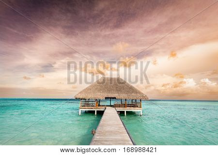 Wooden jetty leading to relaxation lodge. Maldives islands resort on Indian Ocean at sunrise