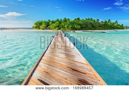 Wooden jetty towards a small island on Indian Ocean, Maldives. Sunny blue sky.