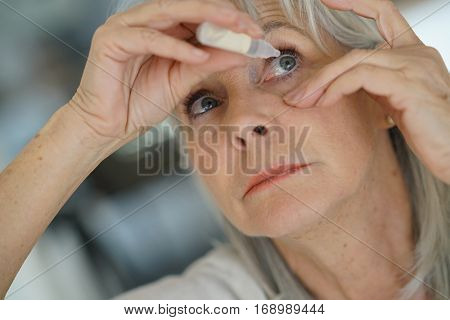Senior woman putting eye drop
