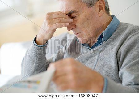 Senior man having a headache reading newspaper