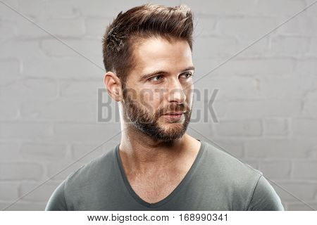 Portrait of young handsome man against white brickwall.