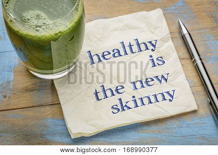 Healthy is the new skinny  - handwriting on a napkin with a glass of fresh, green, vegetable juice