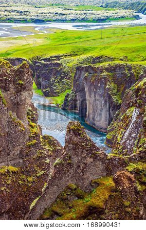 The striking canyon in Iceland. The concept of active northern tourism. Bizarre shape of cliffs surround the stream with glacial water