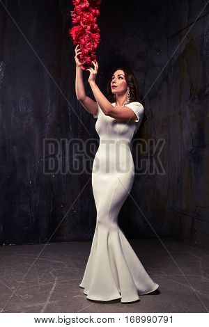 Full-length portrait of sensual brunette posing over worn background. Wearing white fishtail dress. Tempting model is looking up with hands on hips