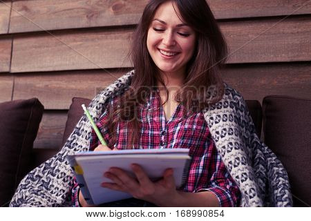 Low angle of lovely smiling girl covered with a blanket holding a jotter while sitting on the sofa. Writing down some information. Holding a green pen