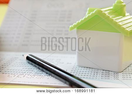 Business, finance, savings money or mortgage concept : Small house and pencil on savings account passbook