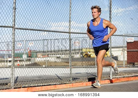 Runner man running - urban city lifestyle. Young sports male athlete jogging in grunge fence background outdoors in summer activewear. Active living.